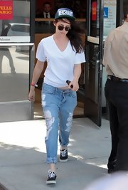 Kristen kept is casual white out in LA, by sporting distressed jeans.