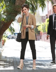 Lily Collins was spotted outside Reese Witherspoon's office looking stylish in a tan blazer layered over a striped shirt.