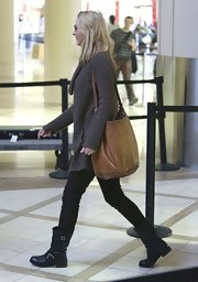 Lisa Kudrow caught a plane at LAX carrying a tan leather shoulder bag.