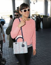 Marion Cotillard teamed a Dior tweed shoulder bag with a pink sweater for her airport look.