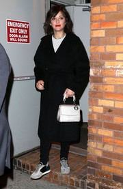 Marion Cotillard left 'The Daily Show with Trevor Noah' wearing a classic belted wool coat.