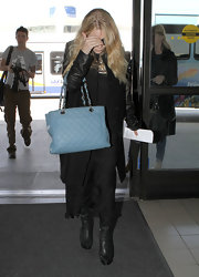 Ashley Olsen arrived for a flight at LAX airport carrying her needs in a leather blue oversized satchel.