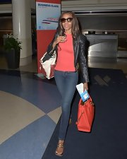 Michelle kept her travel loo simple but polished with a classic black leather jacket paired over a red shirt.