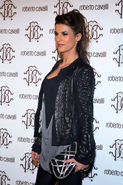 Elisabette Canalis showed off her edgy style in a pair of black leggings and textured leather jacket. She completed her look with a geometric black and silver clutch.