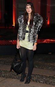 Margherita Missoni showed off her fashion flair with a fur-clad vest and a boho headband. She completed her unique outfit with a black leather messenger bag.