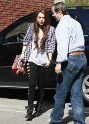 Hitting the recording studio in LA Miley showed off a funky printed tote bag. She paired her colorful bag with shredded black tights and a plaid shirt. Interesting, but it works for her.