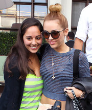 Miley Cyrus wore her hair in a causal top knot while posing with fans in Miami.