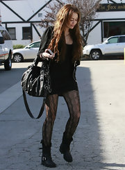 Miley is seen here sporting this awesome Gucci chain strap bag. It works well with her edgy all black look.