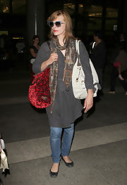 Milla paired her airport outfit with a red velvet shoulder bag.