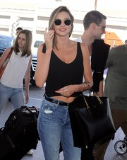 Miranda Kerr accessorized with a pair of Ray-Ban round sunglasses for a flight out of LAX.