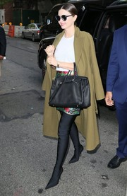 Miranda Kerr layered an olive-green wool coat over a white tee and a printed mini for a day out in New York City.
