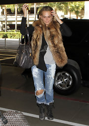 Molly dons a fur vest with torn bleached jeans for her edgy airport ensemble.