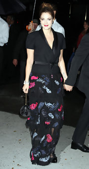 Drew Barrymore layered a short-sleeved black blazer over her floaty feather print gown.