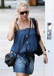 Naomi Watts paired her jean romper with a black cross body bag.