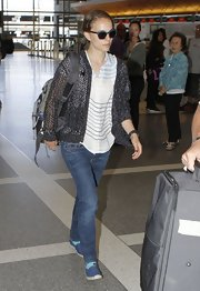 Natalie Portman paired a loose weave cardigan over a slouchy tee for a relaxed travel look.
