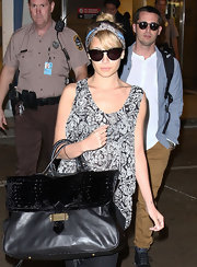 Nicole Richie carried this black patent leather bag for her travels to Miami.