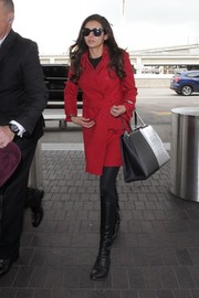 Nina Dobrev teamed her chic coat with black knee-high boots.