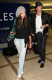 Nina Dobrev strolled through the airport in ripped up boyfriend jeans.
