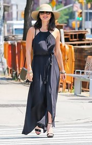 Olivia Munn looked summery chic in this Grecian-style navy maxi dress, which she paired with a wide-brimmed straw hat.