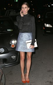 Olivia Palermo accessorized with a white foldover clutch featuring a subtle geometric print.