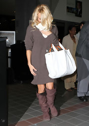Pamela Anderson added some winter white into her travel look with a canvas tote.
