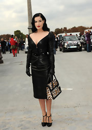 Dita is dressed in a leather Dior suit and is carrying a leopard print bag.