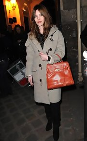 "Lou Lesage arrived at the Givenchy show during Paris Fashion Week sporting a bright orange leather ""Birkin"" tote."