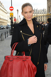 Beautiful Bar Rafaeli jazzes up her black zipper coat with a bright and luxurious red leather tote.