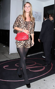 Nicky Hilton added a burst of color to her leopard print dress with a crimson leather handbag. A tasseled zipper sets the purse apart.