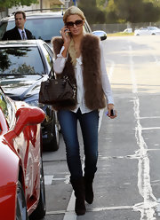 Paris Hilton gave a classic blouse and jeans the boho touch with a furry brown vest.
