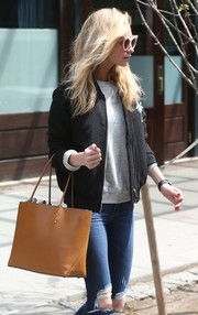 Poppy Delevingne styled her casual outfit with a chic camel-colored leather tote.