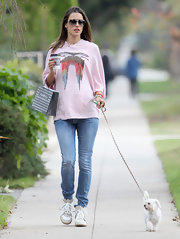 A pregnant Alessandra Ambrosio took her dog from a walk in light wash skinny jeans and white sneakers.