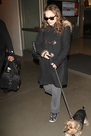 Natalie Portman was comfortable and warm while walking her dog at LAX in a black fur-trimmed toggle coat.