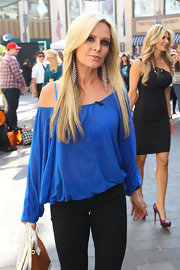 Tamra Barney wore a loose cobalt off-the-shoulder blouse with boho-chic feather earrings.