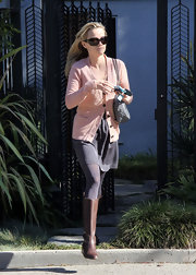 Reese leaves a friends house wearing a pair of chic leather boots.
