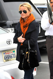 Reese Witherspoon embraced the winter weather in a navy pea coat and a rich orange scarf.
