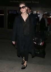 Renee Zellweger traveled in style in this long black wool coat.