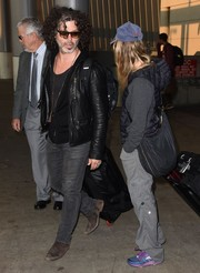 Renee Zellweger arrived on a flight at LAX carrying a black leather hobo bag along with a rollerboard.