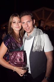 Holly carries a metallic purple oversized clutch.