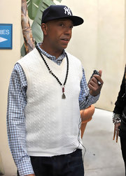 Russell Simmons wears his favorite prayer beads over a cream cable knit sweater vest.