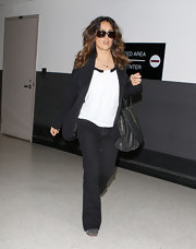 Salma Hayek looked stylish on the go wearing a loose black blazer of a white blouse with black trim.