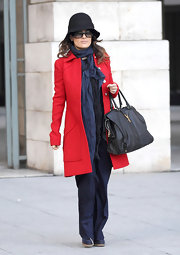 Salma Hayek kept things stylish and simple with a black leather tote and a crimson coat.