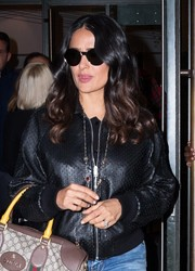 Salma Hayek left a press junket in New York City looking edgy in round shades and a leather jacket.