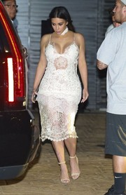 Kim Kardashian's curves were on full display in this sultry white lace dress by Ermanno Scervino during Scott Disick's birthday dinner.