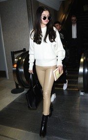 Selena Gomez tied her stylish airport look together with a pair of black ankle boots by Dear Frances.