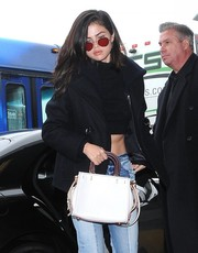 Selena Gomez took a flight out of LAX wearing funky red shades.
