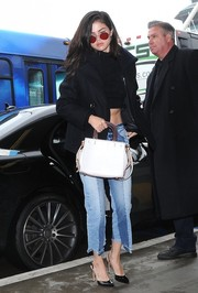Selena Gomez wore a black pea coat for some warmth to her crop-top while taking a flight out of LAX.
