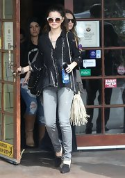 A white fringe shoulder bag completed Selena Gomez's hippie-inspired outfit.