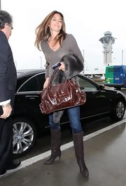 Cindy Crawford kept her travel attire luxurious with the addition of a brow croc bag and fur stole.