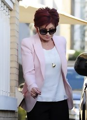 Sharon Osbourne styled her look by wearing a long chain necklace with golden sphere pendant.